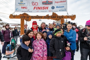 Aliy Zirkle poses with a group of students at the finish line in Nome shortly after finishing the 2019 Iditarod in 4th place on Wednesday March 13Photo by Jeff Schultz/  (C) 2019  ALL RIGHTS RESERVED