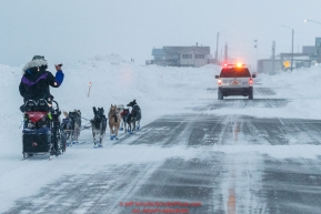 Jessie Royer runs down Front Street with a police car escort as she makes her way toward the Nome finish line to place 3rd in the 2019 Iditarod sled dog race.Photo by Jeff Schultz/  (C) 2019  ALL RIGHTS RESERVED