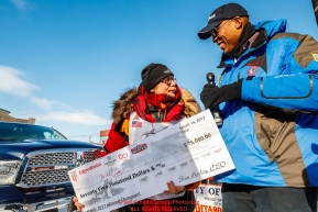 ExxonMobil representative Corey Hines presents Mitch Seavey with his 75,000 winner's purse check after Mitch won his third Iditarod in record time of 8 days, 3 hours, 40 minutes and 13 seconds in Nome during the 2017 Iditarod on Tuesday afternoon March 14, 2017.Photo by Jeff Schultz/SchultzPhoto.com  (C) 2017  ALL RIGHTS RESERVED