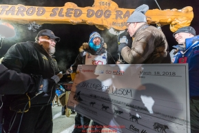 Joar Leifseth Ulsom recieves his winner's check from Kurt Parkan of sponsor Donlin Gold at the finish line in Nome, Alaska early on Wednesday morning March 14th as he wins the 46th running of the 2018 Iditarod Sled Dog Race.  He finished in 9 days 12 hours 00 minutes and 00 secondsPhoto by Jeff Schultz/SchultzPhoto.com  (C) 2018  ALL RIGHTS RESERVED