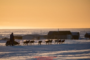 Ketil Reitan runs past fish camps at sunset on the trail heading toward the finish at Nome on Wednesday March 14th during the 2018 Iditarod Sled Dog Race.  Photo by Jeff Schultz/SchultzPhoto.com  (C) 2018  ALL RIGHTS RESERVED