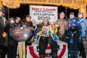 Joar Leifseth Ulsom poses with his lead dogs Russeren (left) and Olive and Iditarod sponsors on the winner's podium at the finish line in Nome, Alaska early on Wednesday morning March 14th as he wins the 46th running of the 2018 Iditarod Sled Dog Race.  He finished in 9 days 12 hours 00 minutes and 00 secondsPhoto by Jeff Schultz/SchultzPhoto.com  (C) 2018  ALL RIGHTS RESERVED
