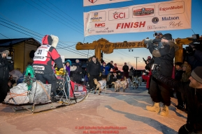 Aliy Zirkle runs into the finish chute and across the line for 15th place  at Nome on Wednesday March 14th during the 2018 Iditarod Sled Dog Race.  Photo by Jeff Schultz/SchultzPhoto.com  (C) 2018  ALL RIGHTS RESERVED