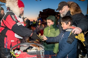 Aliy Zirkle gives away a dog bootie to a young fan in the finish chute in Nome after finishing in 15th place on Wednesday March 14th during the 2018 Iditarod Sled Dog Race.  Photo by Jeff Schultz/SchultzPhoto.com  (C) 2018  ALL RIGHTS RESERVED