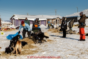 Volunteer vets wait for Martin Buser to finish laying straw for the dogs before they examine his team shortly after his arrival at the Kaltag checkpoint on the afternoon of Sunday  March 15, 2015 during Iditarod 2015.  (C) Jeff Schultz/SchultzPhoto.com - ALL RIGHTS RESERVED DUPLICATION  PROHIBITED  WITHOUT  PERMISSION