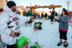 Sebastien Vergnaud tosses a used dog bootie to Kierra Scott in the finish line area in Nome during the 2017 Iditarod on Wednesday March 15, 2017.Photo by Jeff Schultz/SchultzPhoto.com  (C) 2017  ALL RIGHTS RESERVED