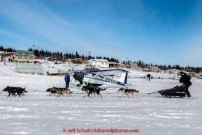 Jessie Royer runs past volunteer pilot Jerry Wortley and plane as she arrives in the afternoon at the White Mountain checkpoint on Tuesday March 16, 2015 during Iditarod 2015.  (C) Jeff Schultz/SchultzPhoto.com - ALL RIGHTS RESERVED DUPLICATION  PROHIBITED  WITHOUT  PERMISSION