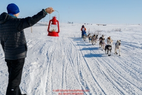Former Nome resident and Iditarod finisher, Melissa Stewart, gives last place finisher and Red Lantern Award winner Cindy Abbott the red lantern on the outskirts of Nome on her way to the finish line during the 2017 Iditarod on Saturday March 18, 2017.Photo by Jeff Schultz/SchultzPhoto.com  (C) 2017  ALL RIGHTS RESERVED