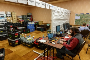 Race Comms coordinator Reece J. Roberts configures a checkpoint laptop at the race headquarters at the Lakefront Anchorage hotel on Thursday March 2, 2017 two days prior to Iditarod 2017 as other comms gear headed out to checkpoints waits to be worked on.Photo by Jeff Schultz/SchultzPhoto.com  (C) 2017  ALL RIGHTS RESVERVED