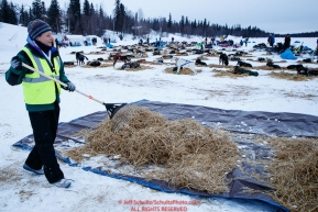 Volunteer Michelle Keagle rakes used dog straw at the Finger Lake checkpoint during the 2018 Iditarod race on Monday March 05, 2018. Photo by Jeff Schultz/SchultzPhoto.com  (C) 2018  ALL RIGHTS RESERVED
