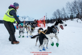 Volunteer Susanna Reider holds back exhuberant dogs of Lars Monson as he checks in at the Finger Lake checkpoint during the 2018 Iditarod race on Monday March 05, 2018. Photo by Jeff Schultz/SchultzPhoto.com  (C) 2018  ALL RIGHTS RESERVED