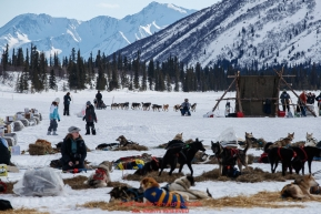Richie Diehl runs toward the check-in tent on Puntilla Lake at the Rainy Pass checkpoint as dog teams rest in the sun during the 2018 Iditarod race on Monday March 05, 2018. Photo by Jeff Schultz/SchultzPhoto.com  (C) 2018  ALL RIGHTS RESERVED